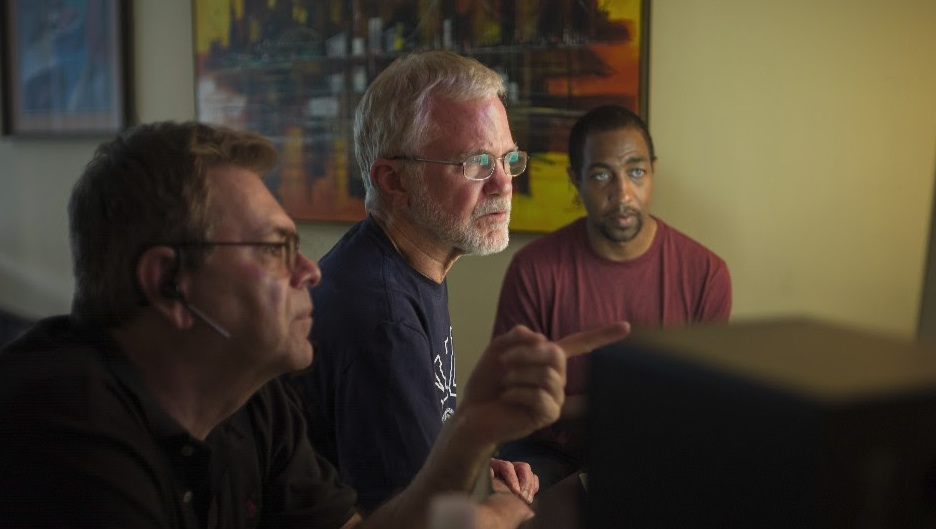 Editor George Artope, Director Peter Brosnan,and Producer Daniel J. Coplan sift through 30 years of footage. Photo by Kelvin Jones.